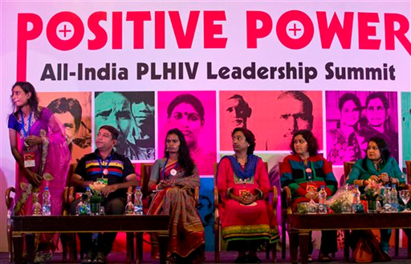 An unidentified person (right) sits on a stage with people living with HIV, (from left to right) Bipasha, Akram, Chandramukhi, Priya and Puja Thakur, at a leadership summit of HIV affected people in New Delhi, India on Monday, November 30, 2015. Photo: AP