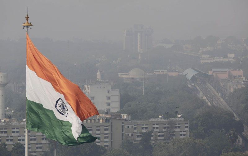 An Indian national flag flies as a thick layer of smog envelops the city skyline after Diwali festival, in New Delhi, India on November 12, 2015. Photo: AP
