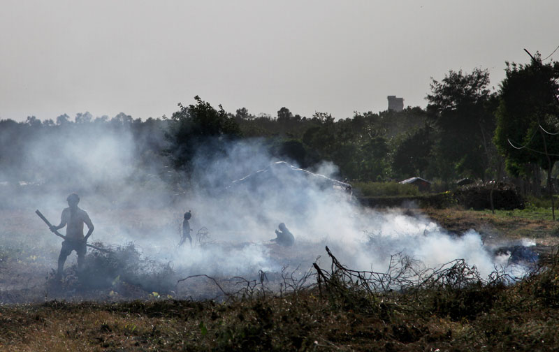 Smoke rises from fire made by burning grass and other dried plants in a field in New Delhi, India on Thursday, September 24, 2015. Photo: AP