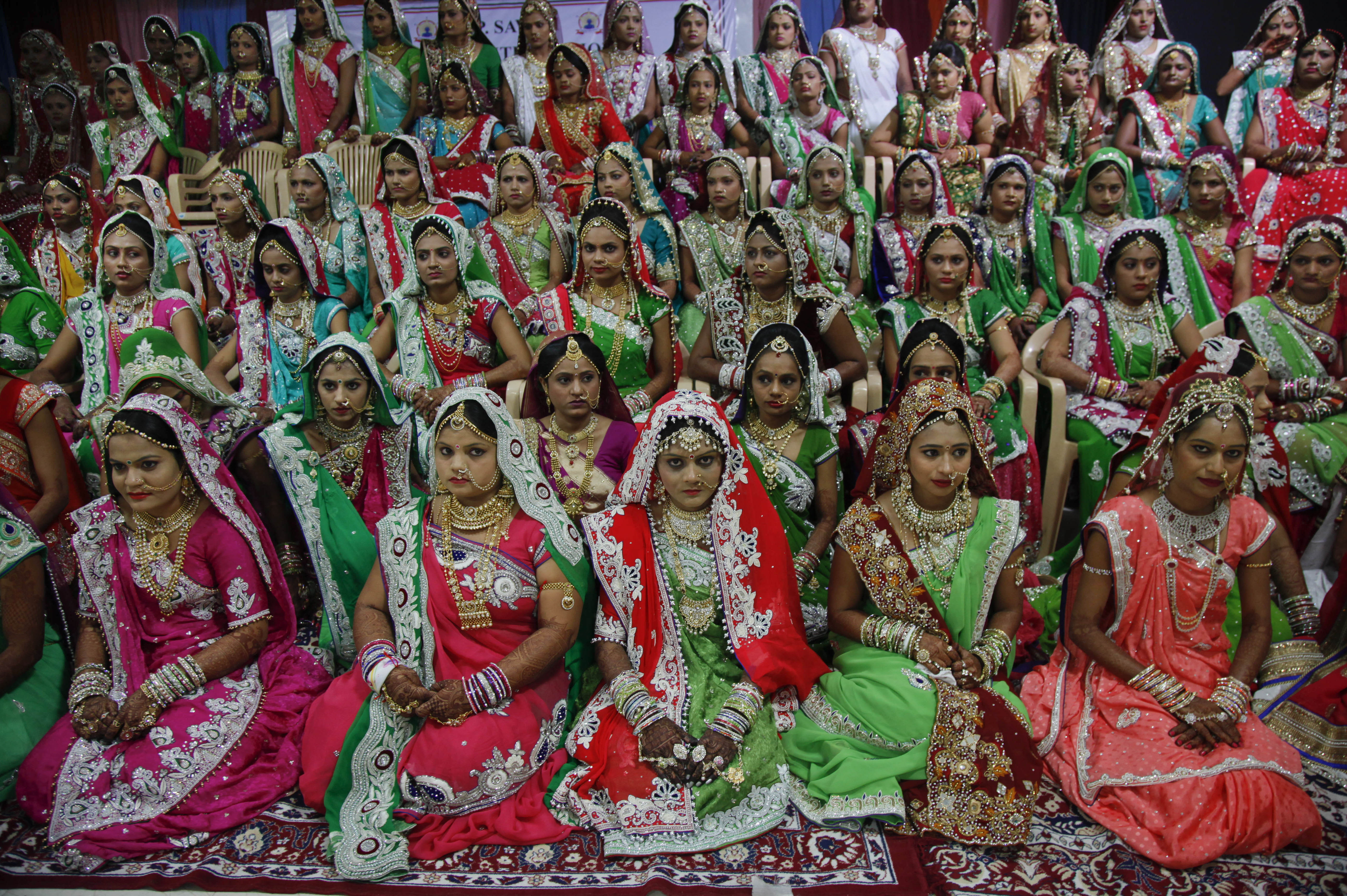 Indian brides sit for a group photo before a mass wedding hosted by a diamond trader in Surat, India, Sunday, Dec. 6, 2015. Photo: AP