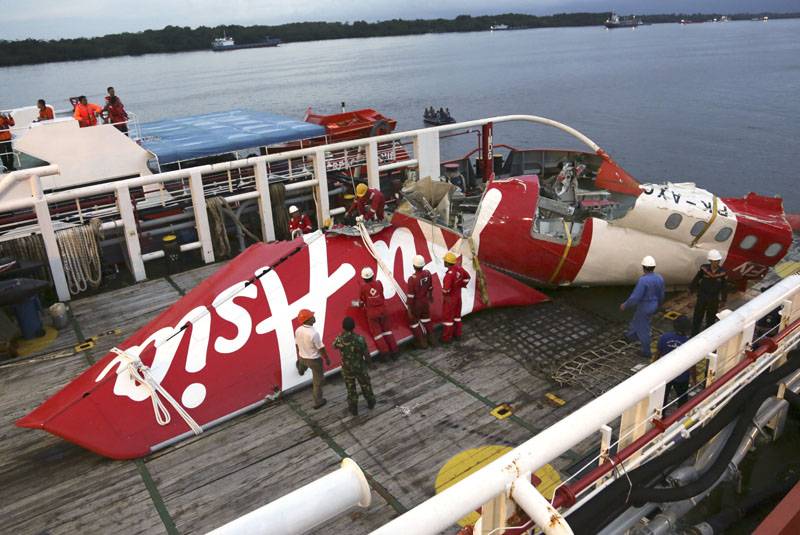 Crew members of Crest Onyx recovery ship prepare to unload the newly-recovered tail section of crashed AirAsia Flight 8501 at Kumai port in Pangkalan Bun, Central Borneo, Indonesia on Sunday, January11, 2015.  Photo: AP