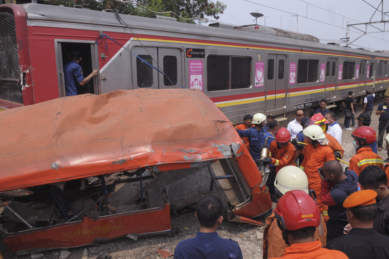 Rescuers remove the wreckage of a passenger minibus after it was hit by a commuter train in Jakarta, Indonesia, Sunday, December 6, 2015. Photo: AP