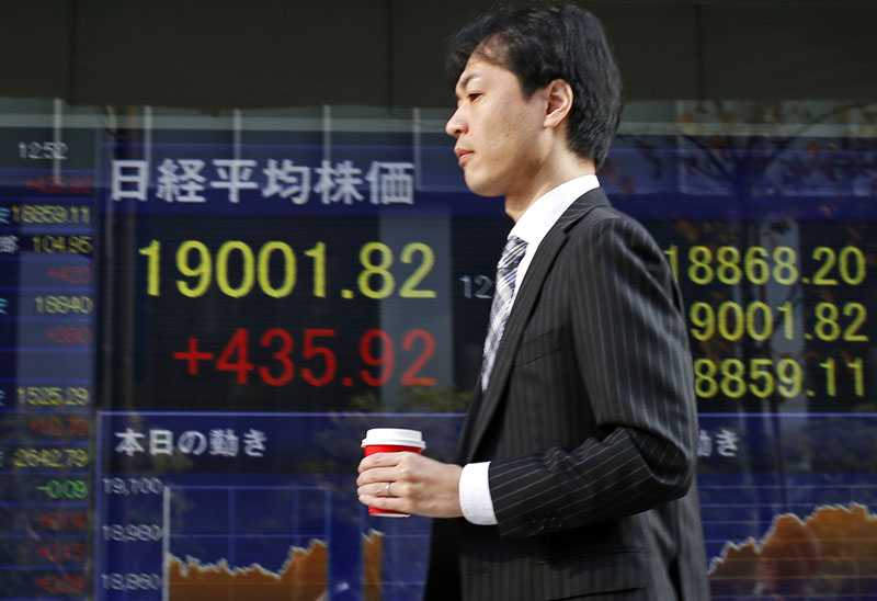 A man walks past Nikkei stock index displayed on an electronic board at a securities firm in Tokyo on Wednesday, December 16, 2015. Photo: AP
