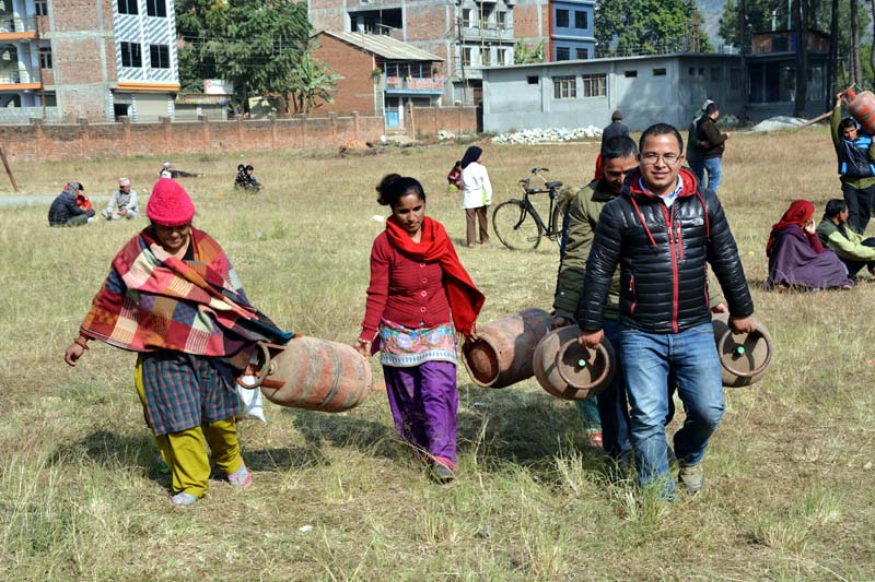 Locals of Baglung taking hard-found cooking gas cylinders home amid the acute shortage of cooking gas on Monday, December 28, 2015. Photo: RSS