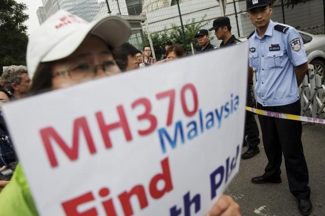 A woman whose relative was aboard Malaysia Airlines flight MH370 holds placard after police stopped protesting relatives from entering a road leading to the Malaysian embassy in Beijing August 7, 2015. Photo: Reuters