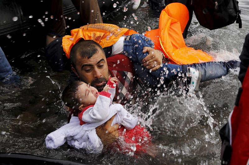 A Syrian refugee holds onto his children as he struggles to walk off a dinghy on the Greek island of Lesbos, after crossing a part of the Aegean Sea from Turkey to Lesbos September 24, 2015. Photo: Reuters