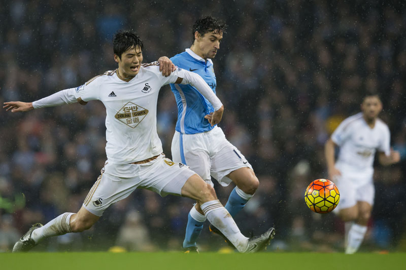 Manchester City's Jesus Navas (centre) fights for the ball against Swansea City's Ki Sung-Yueng during the English Premier League soccer match between Manchester City and Swansea City at the Etihad Stadium, Manchester, England on Saturday December 12, 2015. Photo: AP