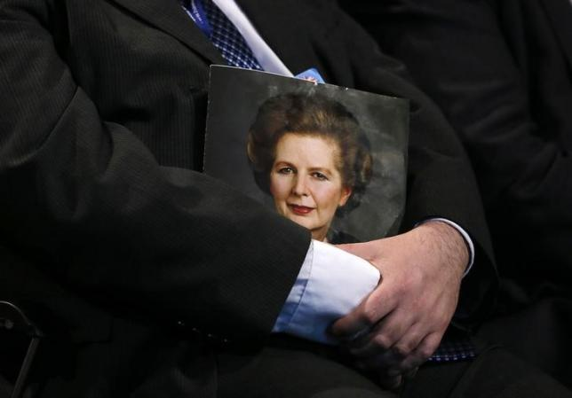 A delegate holds a portrait of Margaret Thatcher during a tribute to the former conservative prime minister on the opening day of The Conservative Party annual conference in Manchester, northern England September 29, 2013.  REUTERS/Phil Noble