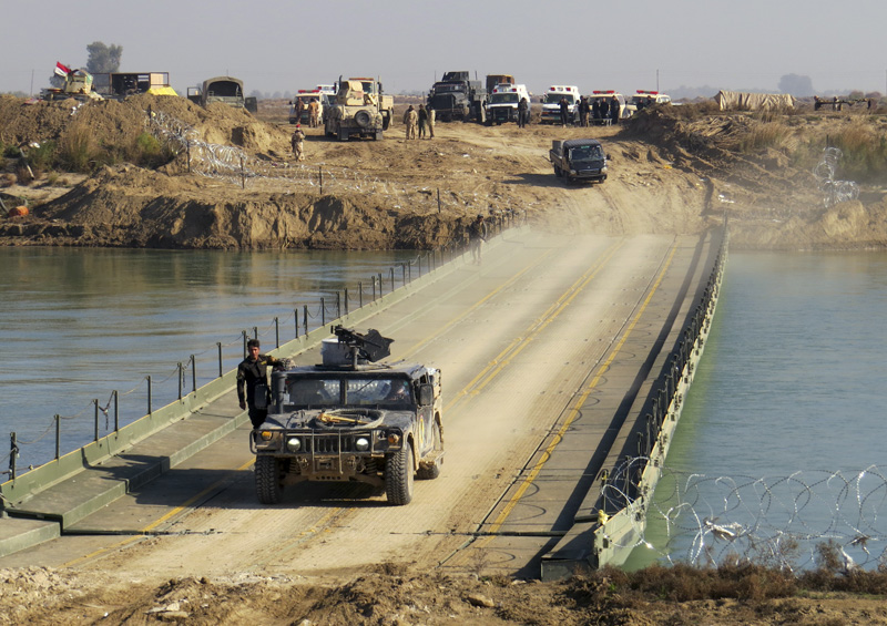 Iraqi security forces cross a bridge built by corps of Engineers over the Euphrates River as Islamic State destroyed all the bridges leading to central Ramadi to block Iraqi security forces from moving forward in Ramadi, 70 miles (115 kilometers) west of Baghdad, Iraq, Tuesday, Dec. 22, 2015. Photo: AP
