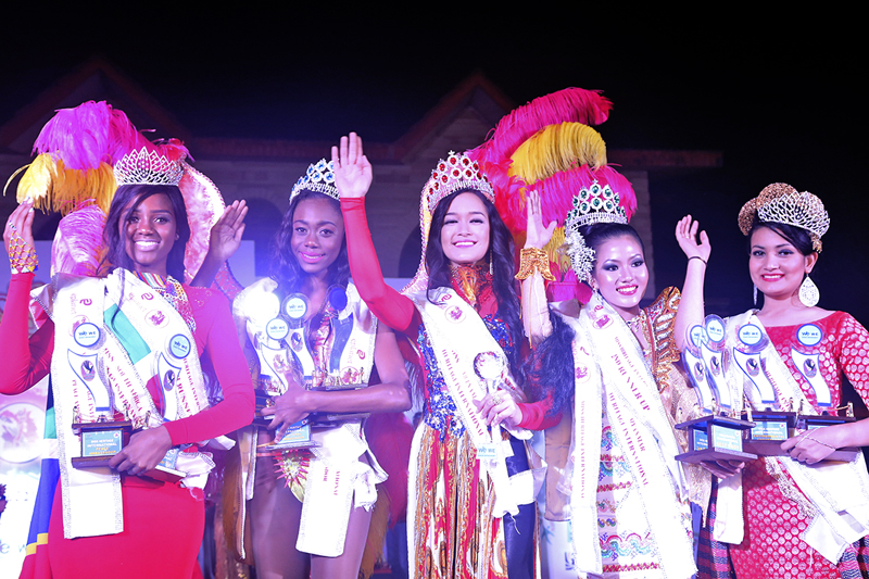 Miss Heritage International 2015, Victoria Pham of Vietnam, flanked by Ketisha Williams of Trinidad and Tobago and Chaw Yupar Tsets of Myanmar, Nisha Pathak of Nepal and Natasha Mogorosi of South Africa, waving to the audience after being crowned the winner in New Delhi, India, on December 12, 2015. Photo: Santosh Sapkota
