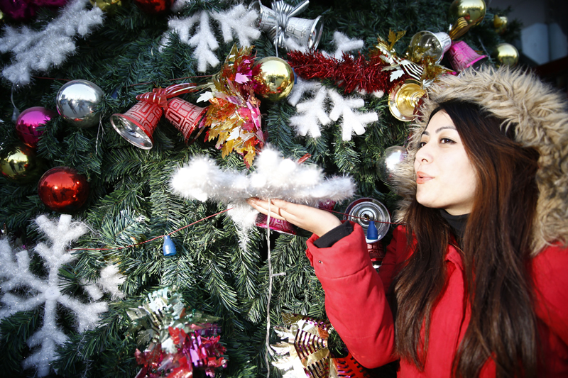 A woman poses as her friend takes a photo in front of a Christmas tree outside a shopping market in Boudha, Kathmandu, Nepal on December 23, 2015. Photo: Skanda Gautam/THT