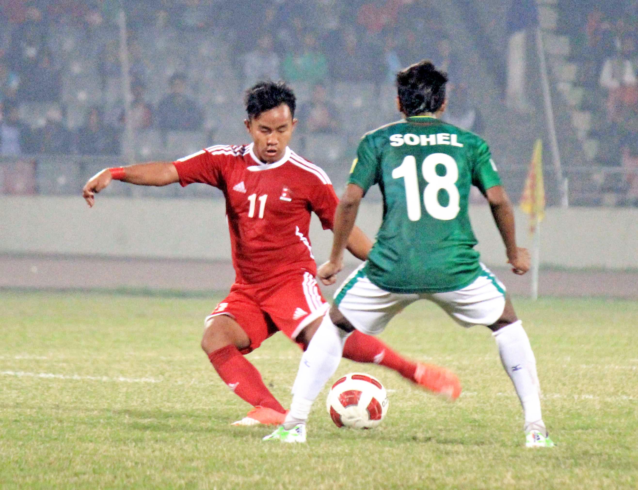 FILE: Nepali player tries to dribble past a Bangladeshi player during their international friendly match at the Bangabandhu Stadium on Thursday, December 17, 2015. Photo: ANFA
