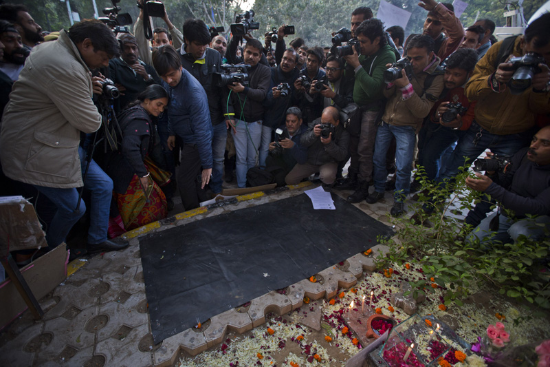 The mother, left wearing saree, of the victim of the fatal 2012 gang rape that shook India, arrives at a temporary shrine dedicated to her daughter at a protest in New Delhi, India, on Monday, December 21, 2015. Photo: AP