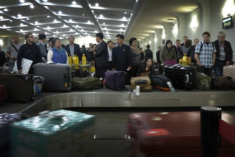 Passengers wait for their luggage upon arrival at the Sunan International Airport in Pyongyang, North Korea on on October 21, 2014. Photo: AP