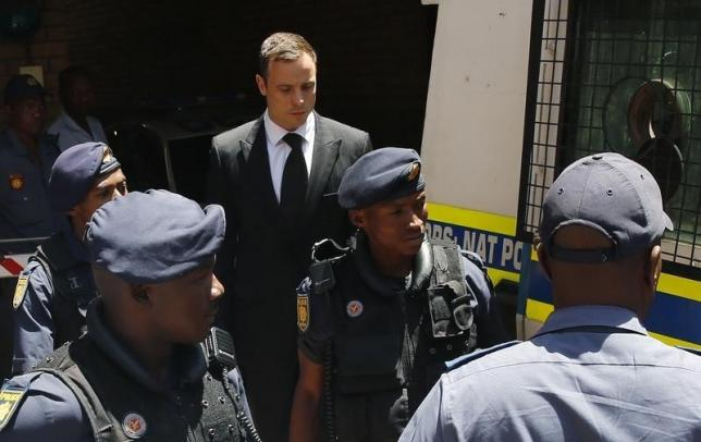South African Olympic and Paralympic sprinter Oscar Pistorius (C ) is escorted to a police van after his sentencing at the North Gauteng High Court in Pretoria in this October 21, 2014 file photo. REUTERS/Siphiwe Sibeko