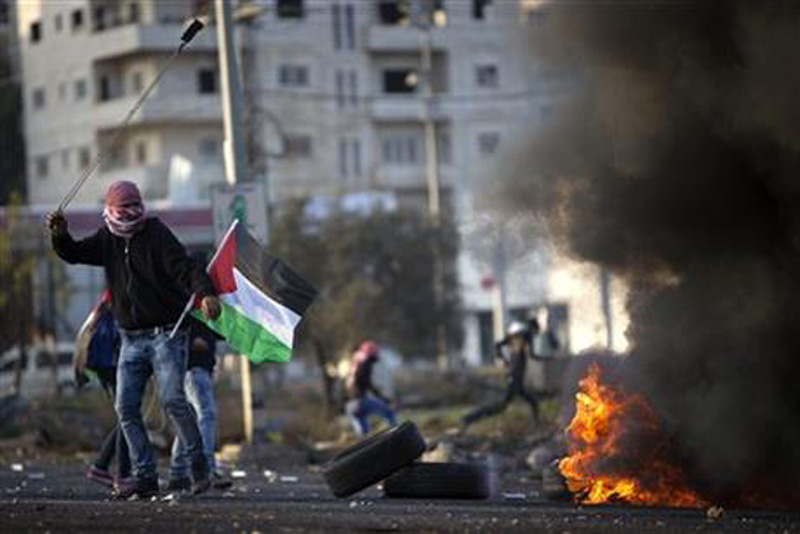 Palestinian protesters throw stones at Israeli troops during clashes following a demonstration to demand the release of bodies of Palestinian attackers being held by Israeli authorities, in the West Bank city of Ramallah, Sunday, Nov. 29, 2015. Photo: AP