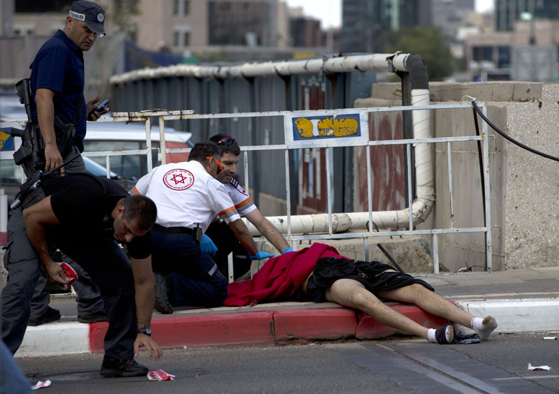 Israeli medics check the body of a Palestinian man who Israeli police said was shot and killed by a soldier after he stabbed four people with a screwdriver, in Tel Aviv Israe on October 8, 2015. Photo: AP