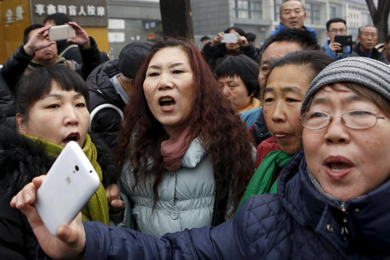 Supporters of China's rights lawyer Pu Zhiqiang shout slogans near a court where Pu's trial is being held, in Beijing, China December 14, 2015. Photo: Reuters