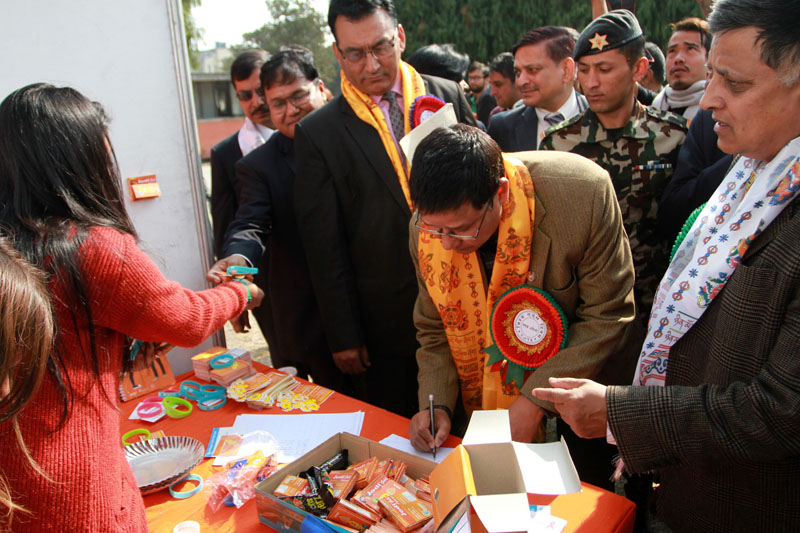 Minister for Health and Population Ram Janam Chaudhary writing  remarks in a programme organised by the Ministry of Health and Population to mark the World AIDS Day in Kathmandu on Tuesday, December 1, 2015. Photo: RSS