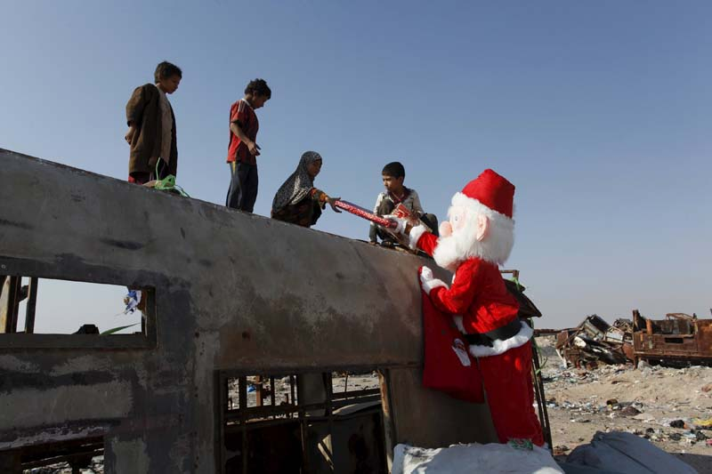 A volunteer wearing Santa Claus costume distributes presents to children at a poor community in Najaf, south of Baghdad, December 19, 2015. Photo: Reuters