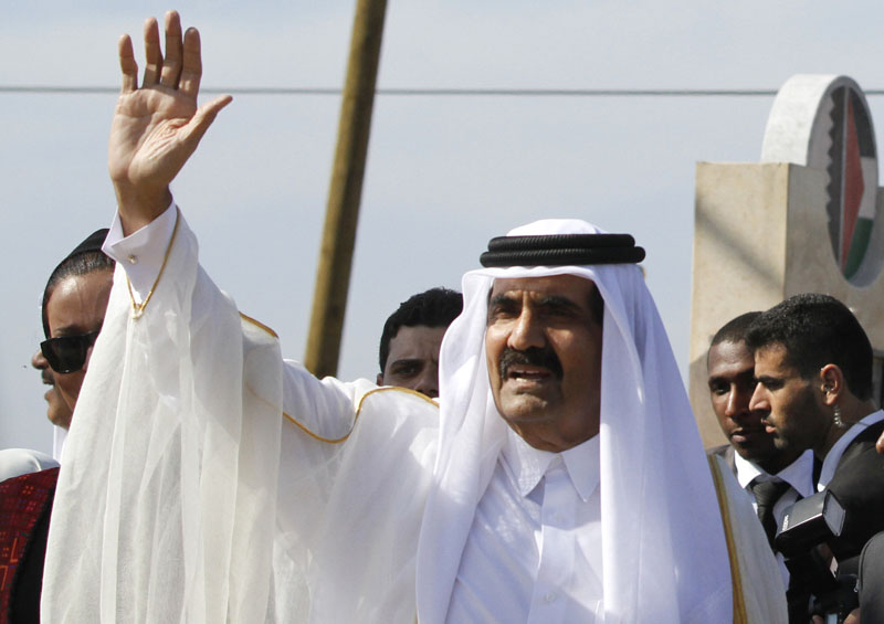FILE - Emir of Qatar Sheikh Hamad bin Khalifa al-Thani waves to the crowd as he and and Gaza's Hamas prime minister Ismail Haniyeh, not pictured, arrive for corner-stone laying ceremony of a Qatari funded rehabilitation center in Gaza City on October 23, 2012. Photo: AP