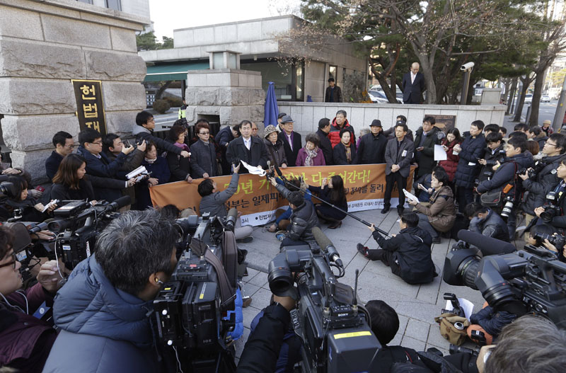 South Korean bereaved family members of victims of World War II hold a press conference in front of the Constitutional Court in Seoul, South Korea on Wednesday, December 23, 2015. Photo: AP