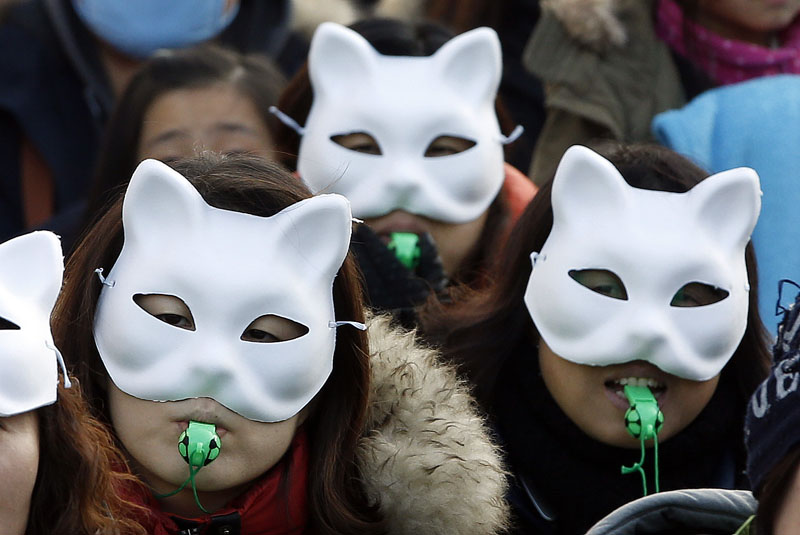 Protesters wearing white half masks, blow whistles during anti-government rally in downtown Seoul, South Korea on Saturday, December 19, 2015. Photo: AP