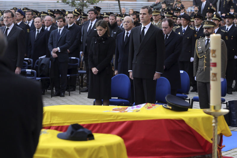 Spain's King Felipe VI and Queen Letizia (centre), stand with Spain's Prime Minister  Mariano Rajoy, (left), behind the flag draped coffins of the two Spanish police officers killed in Kabul during a funeral in Madrid, Spain on Tuesday December 15, 2015. Photo: AP