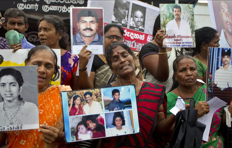 Sri Lankan ethnic Tamil women hold photographs of their family members who have gone missing, during a protest to mark international Human Rights Day in Colombo, Sri Lanka on Thursday, December 10, 2015. Photo: AP