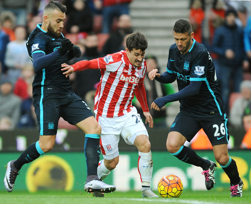 Stokeu2019s Philipp Wollscheid (centre) is tackled by Manchester Cityu2019s Martin Demichelis (right) and Nicolas Otamendi (left) during the English Premier League soccer match between Stoke City and Manchester City at the Britannia Stadium, Stoke on Trent, England on Saturday, December 5, 2015. Photo: AP