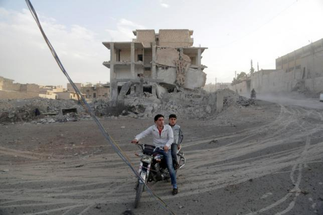 Men ride a motorcycle in a site hit by what activists said were airstrikes carried out by the Russian air force in the rebel-controlled area of Maaret al-Numan town in Idlib province, Syria October 24, 2015. REUTERS/Khalil Ashawi