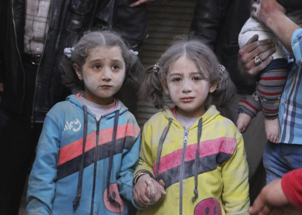 Girls who survived what activists said was a ground-to-ground missile attack by forces of Syria's President Bashar al-Assad, hold hands at Aleppo's Bab al-Hadeed district April 7, 2015. REUTERS/Abdalrhman Ismail/Files