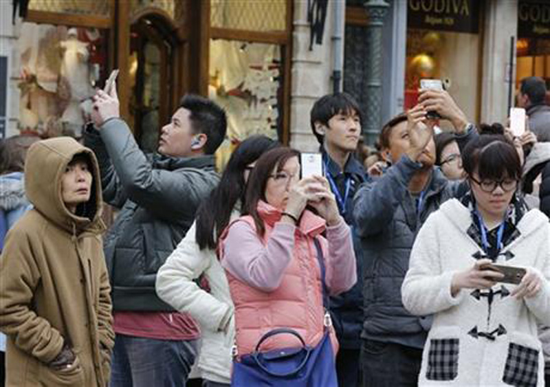 Japanese tourists take pictures on the Grand Place in Brussels, Belgium, Friday, Nov. 27, 2015. Brussels lowered its terror alert from four, the highest, to three. Photo: AP