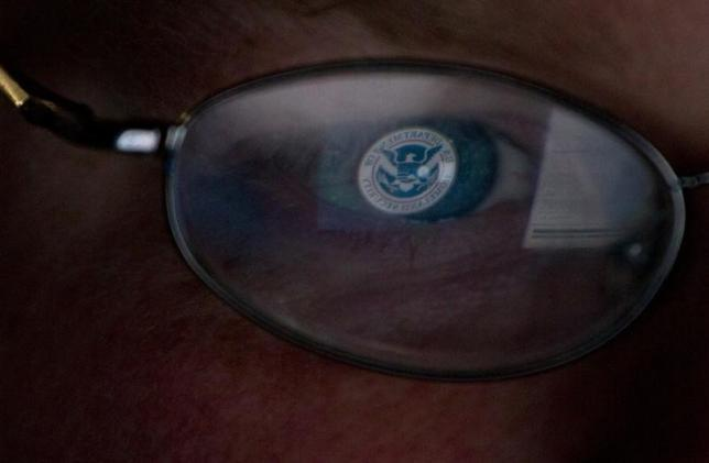 The logo of the U.S. Department of Homeland Security is reflected in the spectacles of an analyst working in a watch and warning center of a cyber security defense lab at the Idaho National Laboratory in Idaho Falls, Idaho September 29, 2011. REUTERS/Jim Urquhart