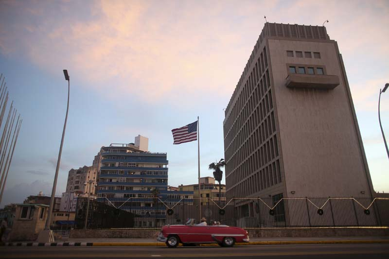 Tourists drive in a vintage car past the US embassy while on a sightseeing tour through Havana, on December 18, 2015. Photo: Reuters