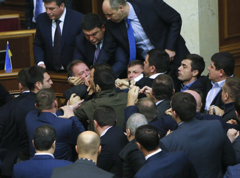 Ukrainian lawmakers fight each other right  after Prime Minister Arseniy Yatsenuk's speech during  a parliamentary session in the Parliament in Kiev, Ukraine, Friday Dec. 11, 2015. Photo: AP
