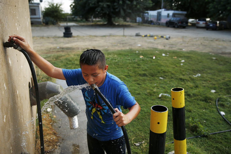 In this photo, 9-year-old Carlos Velasquez drinks well water from a hose at a trailer park near Fresno, California, on Monday, September 14, 2015. Photo: AP/ File