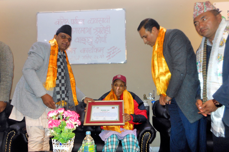 Minister for Culture, Tourism and Civil Aviation Ananda Prasad Pokharel honouring Wanchu Sherpa with 'Sagarmatha (Mt. Everest) Conservation Campaigner Award-2072u2019 amid a function in the Capital on Thursday, December 10, 2015. Photo: RSS