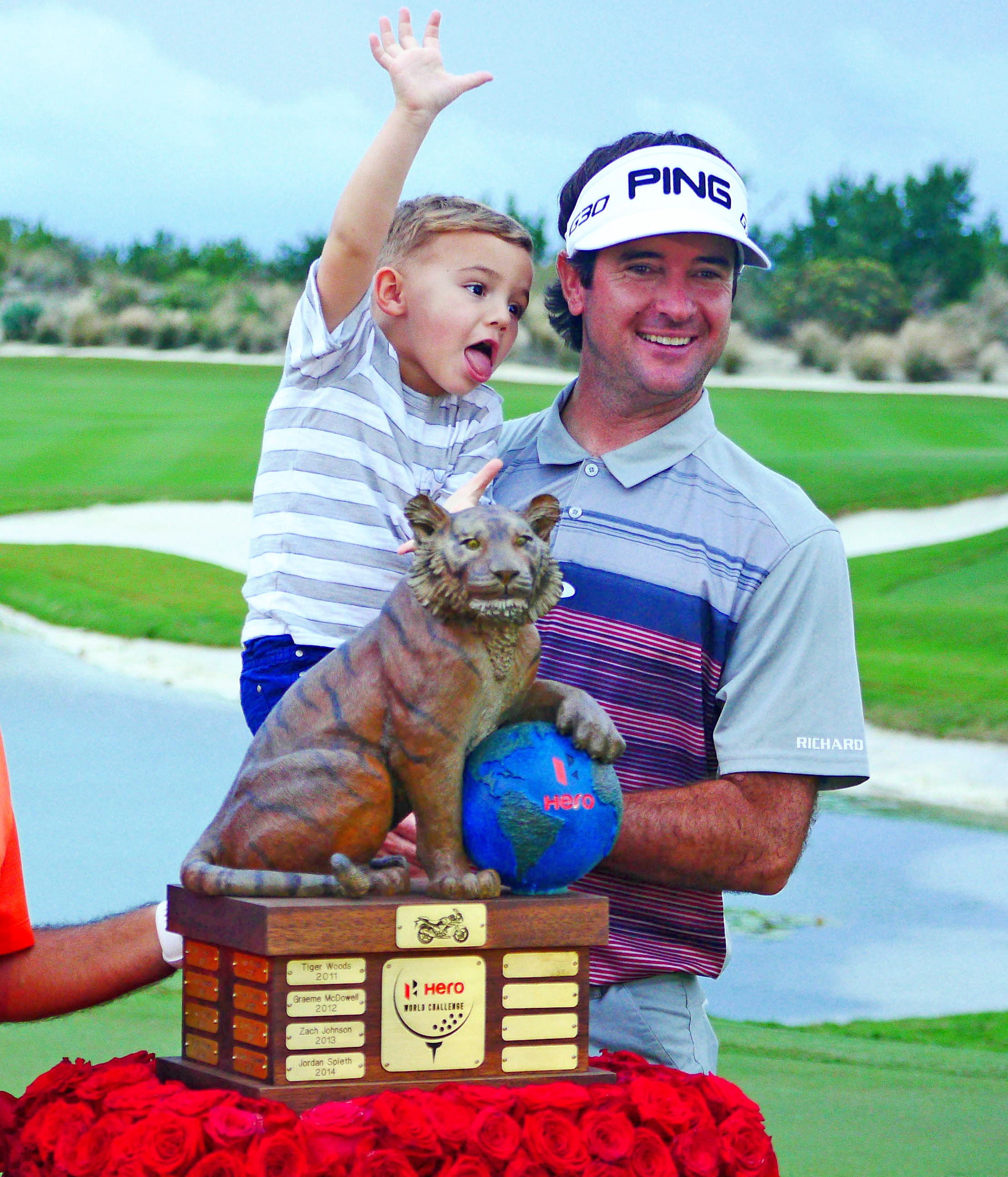 Bubba Watson, right holds his son Caleb, as he stands next to Hero Motorcycle Co. executive Pawan Munjal, left, as they pose behind the Hero World Challenge trophy in Nassau, Bahamas, Sunday, Dec. 6, 2015. Watson, the winner by 3 shots, was never seriously challenged at Albany Golf Club and sailed home to a 6-under 66 for a three-shot victory over Patrick Reed. (AP Photo/Kevin Taylor)