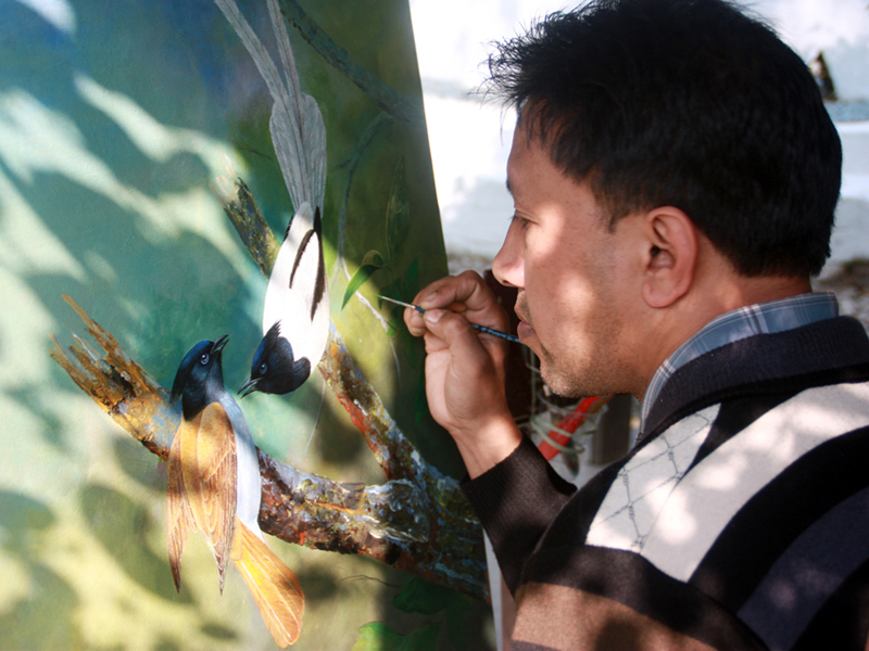 Artist Sanju Shahi paints birds on his canvas during the 'Art for Nature' international workshop in Sauraha of Chitwan, on Saturday, December 12, 2015. Photo: RSS