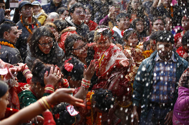 People are offered blessings by a girl during her Bel Bibaha ceremony at the Basantapur Durbar Square, Kathmandu, Nepal on Saturday, December 5, 2015. Bel Bibaha is a ceremony in Newari community of Nepal, in which pre-adolescent girls are married to the bel fruit, Aegle marmelos, before they begin menstruation. Photo: Skanda Gautam