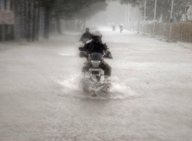 A man rides his motorbike through a flooded road during heavy rain in Chennai, India, November 9, 2015. REUTERS/Stringer