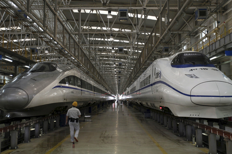 A worker walks between two bullet trains at a high speed railway maintenance station in Xi'an, Shaanxi province, China, in this September 10, 2015. Photo: Reuters/ File