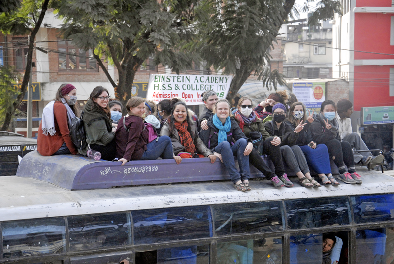 Since fewer public vehicles ply the roads in the Kathmandu Valley due to fuel scarcity, passengers are forced to sit on the hood of  a packed bus, in Lalitpur. Photo: THT