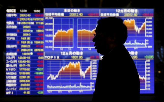 A man walks past an electronic board showing graphs of recent Japan's Nikkei share average outside a brokerage in Tokyo, Japan, on December 1, 2015. Photo: Reuters