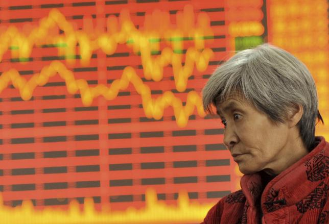 An investor stands in front of an electronic board showing stock information at a brokerage house in Fuyang, Anhui province, China, December 4, 2015. Photo: Reuters