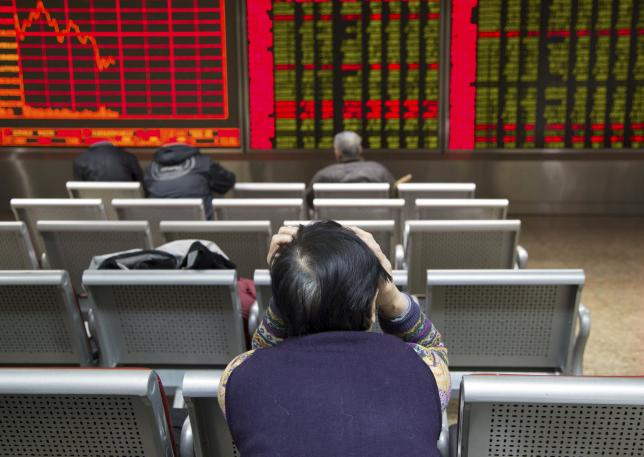 An investor sits in front of an electronic board showing stock information at a brokerage house in Beijing, China, November 30, 2015. REUTERS/Li Sanxian