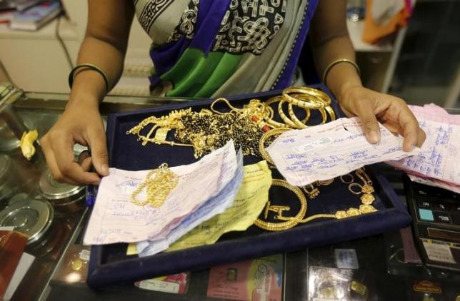 A saleswoman checks the weight and quality of  gold jewellery inside a showroom in Mumbai, August 13, 2015. REUTERS/Shailesh Andrade/Files