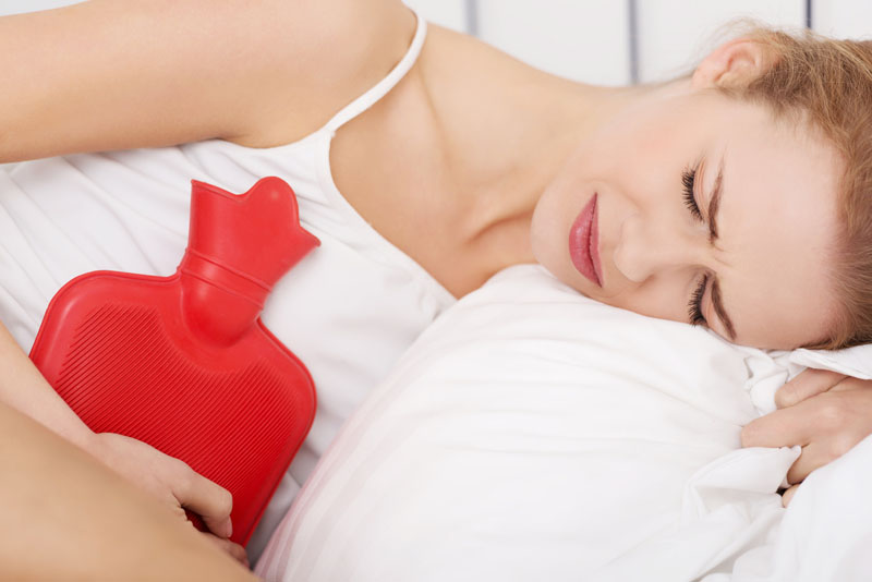 Beautiful caucasian woman lying in bed with hot water bag and holding it on her belly.