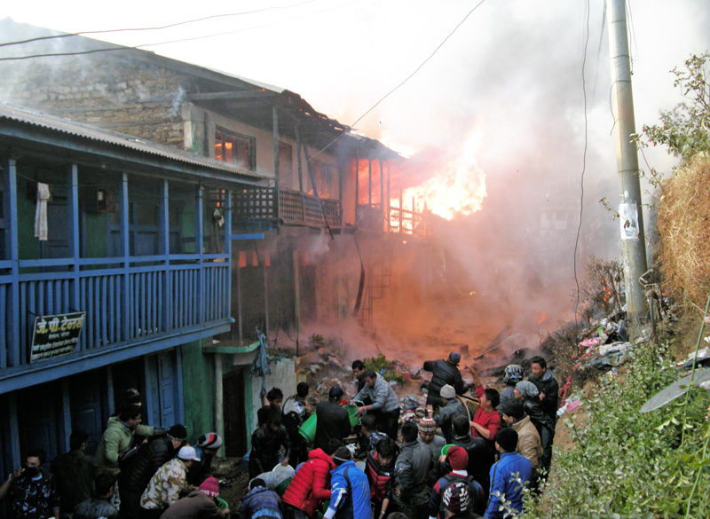 Locals tying to douse the fire sparked in Khotang district headquarters, Diktel, on Thursday, December 17, 2015. Photo: Dilip Khatri